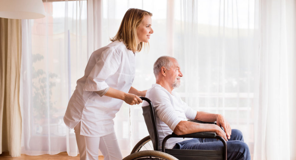 young woman pushing the old man on the wheelchair