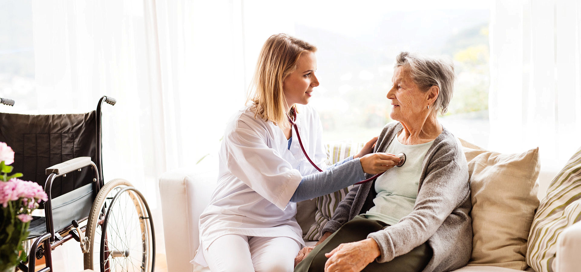 young nurse checking up old woman