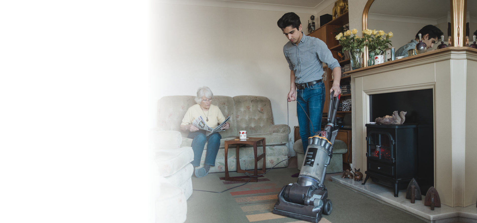 teenage boy is hoovering his grandmother`s living room for her while she reads a newspaper