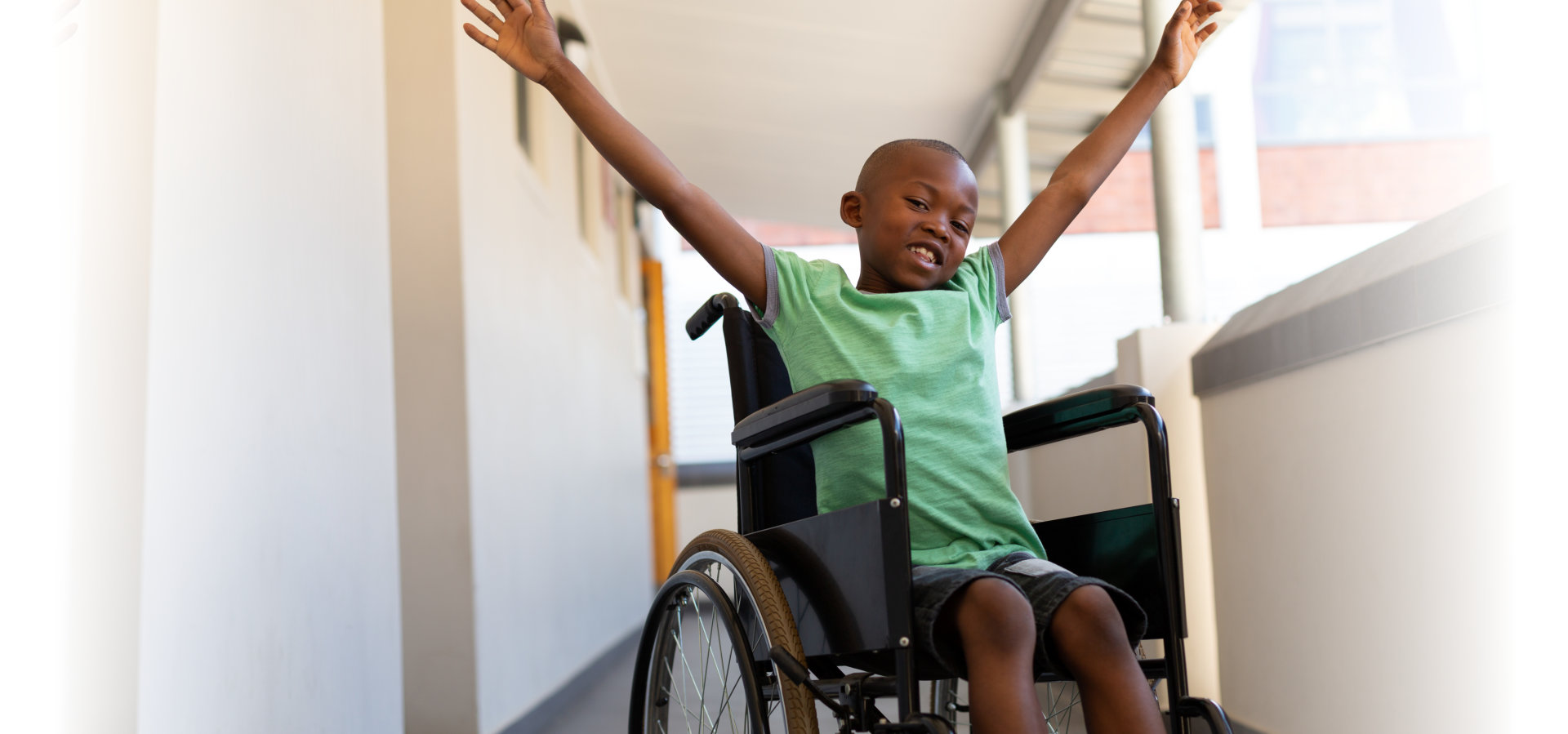 boy with arms stretched out sitting in a wheelchair