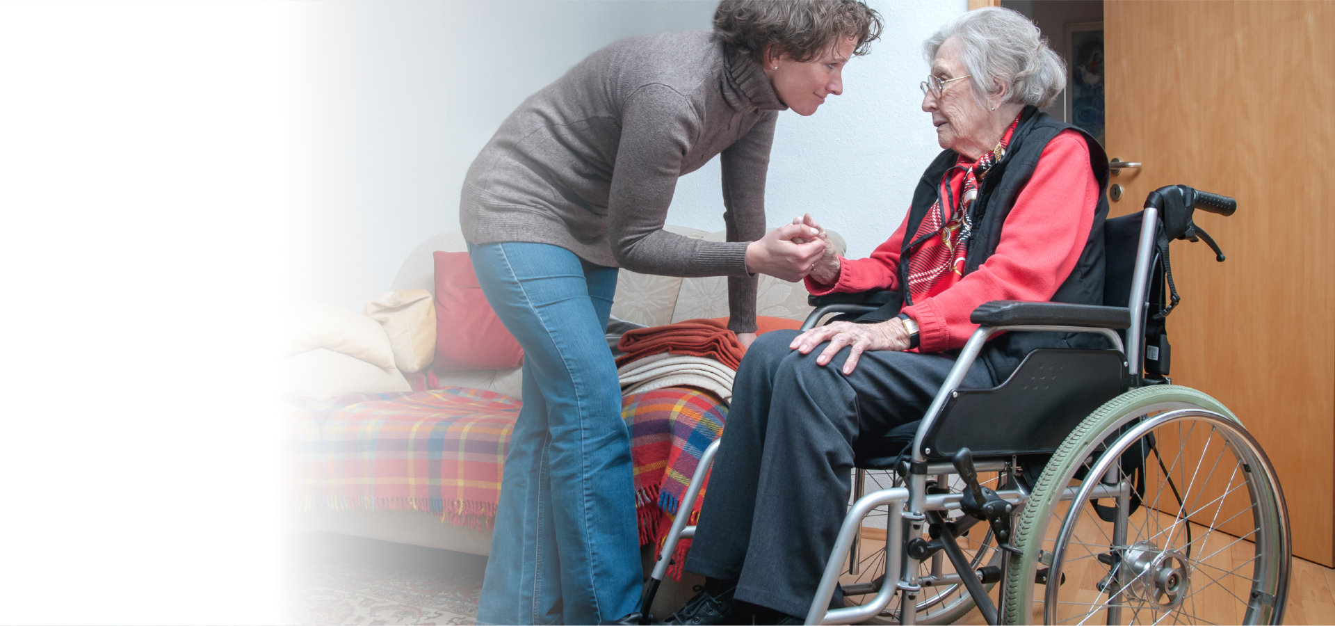 caregiver holding hand of senior woman sitting in wheelchair
