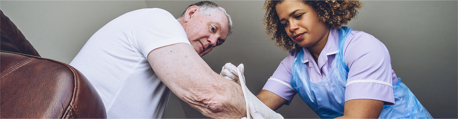 caregiver putting a bandage on a senior mans arm