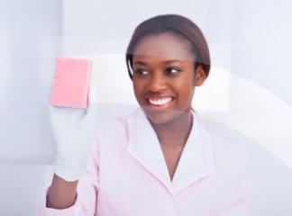 female housekeeper cleaning glass in hotel