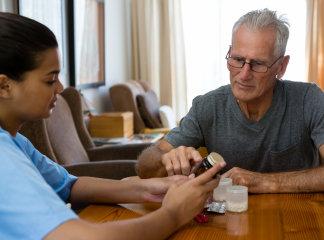 caregiver guiding senior man in taking his medicine