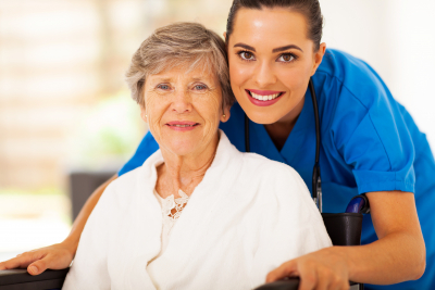 senior woman on wheelchair smiling with caregiver